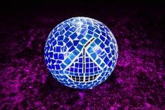 Fortune teller sphere on carpet. Blue mosaic shiny fortune teller globe on purple soft carpet stock image