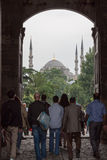 Blue Mosque Istanbul. Tourists and the Blue Mosque with its domes and four minarets framed by an arch door Stock Photography