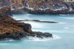 Blue motion blur water surrounding rocks Royalty Free Stock Photo