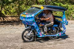 Blue motor-tricycle taxi on the move in Puerto Princesa, Palawan, Philippines