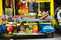 Blue motorbike display with fruits, vegetables, lampoons, buddha head in front of Chinese shop, Chinese Full Moon festival stock image