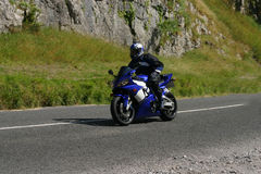 Blue motorbike, one hand. Blue motorbike at speed, rider holding on with one hand Royalty Free Stock Images