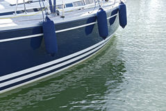 Blue motorboat on calm water. Side of a blue motorboat with fenders on calm green water royalty free stock photography