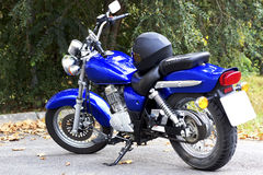 Blue motorcycle and black helmet. A blue motorcycle parked and a black helmet on his seat stock images
