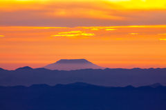 Blue mountain with orange sky while rising sun Royalty Free Stock Image