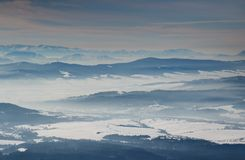 Blue mountain ridges and snowfields in hazy valleys in Slovakia. Sunlit winter scenery elevated view with blue mountain ridges, snowfields in misty valleys and royalty free stock photography
