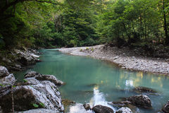 Blue mountain river flowing among big stones in tropical greenforest Stock Images
