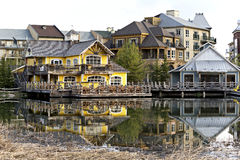 Blue Mountain Village - A Four Season Resort in Ontario, Canada. Condominiums and restaurants bathed in natural light of early Spring and reflected in the pond Royalty Free Stock Images