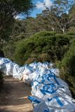 Blue Mountains, Australia - April 24 2019: Bags of track maintenance supplies and materials waiting for use beside a walking track stock image