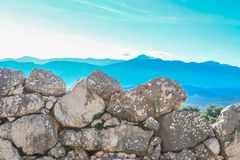 Blue mountains in the distance viewed from the rock walls of ancient hill fort of Mycenae mentioned in Homers Iliad royalty free stock image
