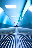 Blue moving escalator in the office hall Royalty Free Stock Image