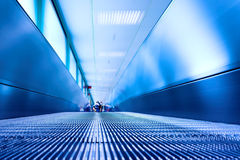 Blue moving escalator in the office hall Royalty Free Stock Photography