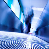 Blue moving escalator in the office hall. Perspective view stock photo