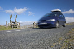Blue MPV speeding on mountain road Royalty Free Stock Photos