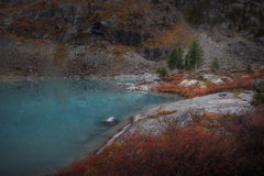Blue Muddy Mountain Lake WIth Red Color Growth On The Shore, Altai Mountains Highland Nature Autumn Landscape Photo. Beautiful Russian Wilderness Scenery Image Royalty Free Stock Photography