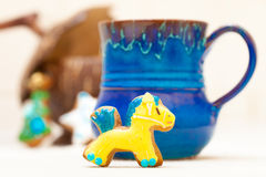 Blue mug and christmas gingerbread cake pony icing decoration. Blue mug of hot beverage drink tea or coffee and homemade gingerbread cake pony with icing and stock photos
