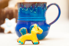 Blue mug and christmas gingerbread cake pony icing decoration. Blue mug of hot beverage drink tea or coffee and homemade gingerbread cake pony with icing and Stock Image