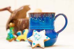 Blue mug and christmas gingerbread cake star icing decoration Stock Photos