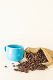 Blue mug coffee with bag sacks of coffee beans on white background. Emphasizing copy space on up side for write text Royalty Free Stock Photography