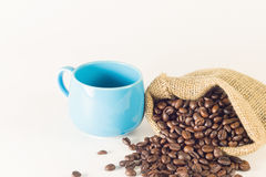 Blue mug coffee with bag sacks of coffee beans on white background. Emphasizing copy space on up side for write text Stock Image