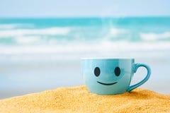 Blue mug of hot coffee or tea on sand beach . Stock Images