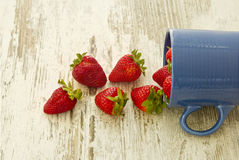 Blue mug pouring out red ripe strawberries Royalty Free Stock Photos