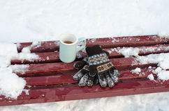 Blue mug tea and women`s knitted gloves on a bench in the winter, snow in the background. Close-up Stock Image