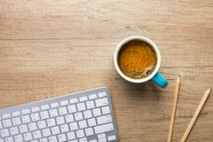 Free Blue Mug With Freshly Brewed Frothy Coffee With Crema White Computer Keyboard Pencils On Wood Desk. Designer Copywriter Student Royalty Free Stock Photography - 161058187