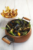 Blue mussels in a copper cooking pot with French fries Royalty Free Stock Images