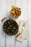 Blue mussels in a copper cooking pot with French fries Stock Photo