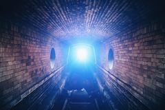Blue mysterious light at the end of dark brick underground tunnel stock images
