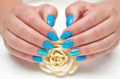 Blue nail polish with glitter on the ring finger with a yellow rose in his hand Stock Photo