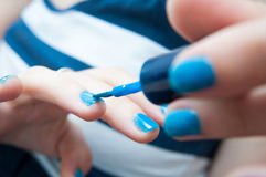 Blue nail polish. Putting blue nail polish in the middle of the action Royalty Free Stock Photo