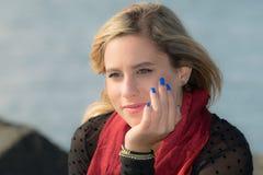 Blue nail polish. A young woman with blue nail polish and staring behind his thoughts Royalty Free Stock Photos