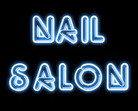 Blue NAIL SALON neon sign. On black backdrop Royalty Free Stock Photo