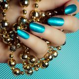 Blue nails manicure. Beautiful female hand with blue nails or turquoise nails is holding a golden pearl jewel on blue or turquoise background. Manicure and nail royalty free stock photo
