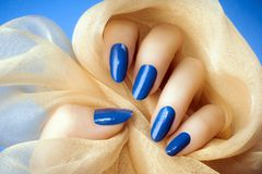 Blue nails manicure. Female hand with dark blue nails is holding a beige decoration on blue background, manicure and nail care concept royalty free stock images
