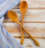 Blue napkin on a white wooden table. Blue napkin with wooden spoons on a white wooden table royalty free stock images