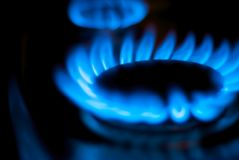 Blue Natural Gas Flames on Kitchen Stove. A close up shot of blue flames from a natural gas burner in a home kitchen Stock Photo