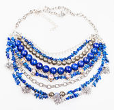 Blue necklace from natural gemstones on white. Blue necklace from natural gemstones (lapis lazuli - lazurite, pyrite, glass lampwork beads) on white background Royalty Free Stock Photo
