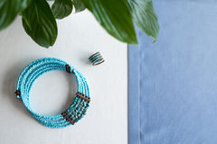 Blue necklace and ring stone beads on a white and blue background with plants Royalty Free Stock Image