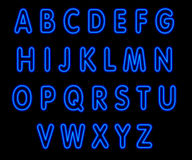 Blue neon capital alphabet on black Royalty Free Stock Images
