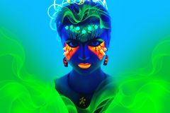 Blue neon make up. Creative woman model shine blue green orange colors. Bright conceptual art make-up glows under ultraviolet light. Club disco neon party time Stock Photo