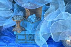 Blue netting and glass rocks display. Blue netting and glass rocks window display stock photos