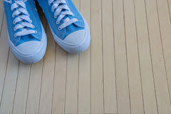 Blue new sneakers on the wooden background Royalty Free Stock Photo