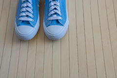 Blue new sneakers on the wooden background Stock Photos