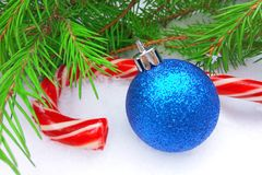 Blue New Year ball and Christmas caramel candy with green fir tree on snowy background royalty free stock photos