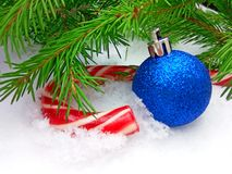 Blue New Year ball and Christmas caramel candy with green fir tree on snowy background. Close up photography with copy space stock photography