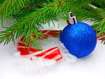 Blue New Year ball and Christmas caramel candy with green fir tree on snowy background. Close up photography royalty free stock photo