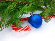Blue New Year ball and Christmas caramel candy with green fir tree on snowy background. Close up photography with copy space stock images